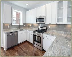 white kitchen cabinets with gray granite backsplash black countertops and