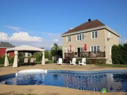vue de la rue grande maison avec piscine creusée