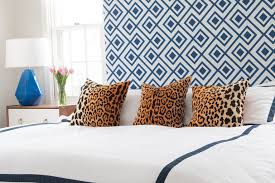 blue and white headboard with blue and white bedding and leopard throw pillows