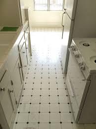 an all white kitchen with basic linoleum flooring