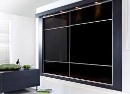 black glass sliding wardrobe doors with silver alumunium frame plus four ceiling lamps on black white bedroom wall