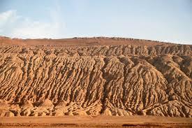 Buildings dwarfed by vast Gobi desert landscape along the Silk Road near  Turfan, Xinjiang, China, Asia -