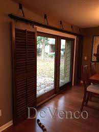 pool room with rolling shutters four panel glass sliding door eight plantation shutter panels off to