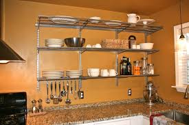 Kitchen. three rows silver steel wall mounted shelves with hook on brown kitchen  wall.