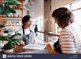 Hostess Talking Looking At Seating Chart Stock Photo