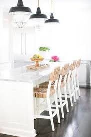 white center island seats four seagr counter stools on dark stained oak floors in front of