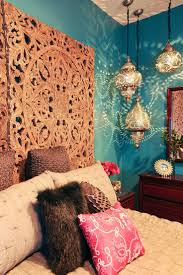 Rich teal walls, Moroccan lanterns and a dramatic headboard made from a  pair of antique