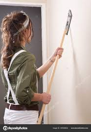 young woman is sanding wall with pole sander before painting in house under remodeling photo by bjphotographs