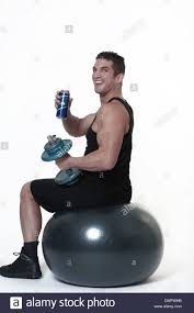 man sitting on a gym ball being tempted to give up and have a drink