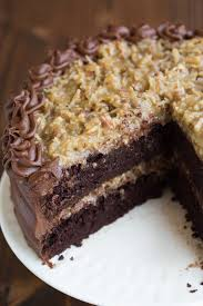 a large german chocolate cake with one large slice missing from the front