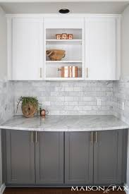 Two-toned gray and white cabinets, marble subway tile, Carrara countertops,  a