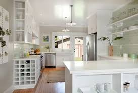 Tropical Kitchen with Crown molding, Pendant Light, Limestone counters,  Flat panel cabinets,