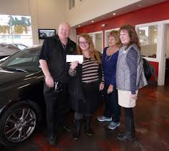 brion jerome from wheels deals presents a check to clothes for kids employee lisa george volunteer donna radovich and board member kathy hashbarger