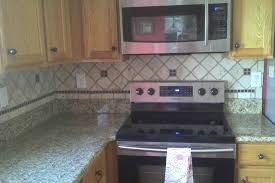 interior grey granite countertop with pencil edges and grey tiles backsplash on brown wooden cabinet