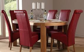modern dining table and chair with 6 parsons chairs made of red leather and oval wooden table
