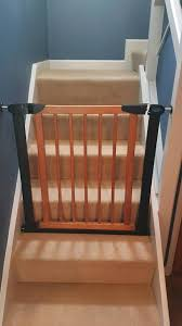 wooden stair gate with dark metal frame pressure fit used occasionally at grandma s