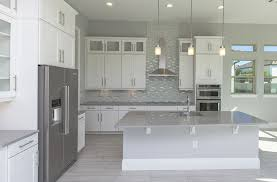 Contemporary kitchen with white cabinets and adhesive mosaic backsplash