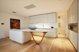 the beautiful custom wood base of this island serves as a sculptural element as well as a functional support the slender v shape base provides good