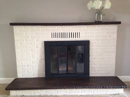 updated fireplace old white chalk paint on the brick and walnut wood stain on the