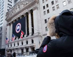a woman wearing a canada goose coat stops to photograph the company s banner at the new york stock exchange in 2017 mark lennihan