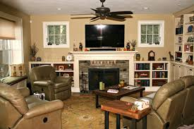 this family room features custom built in bookshelves adjoining the fireplace surround and floor