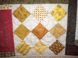 Learn Helpful Tips for Setting Quilt Blocks On Point & White Quilt with Yellow-Hued Pattern Diamond Blocks and Colorful Border Adamdwight.com