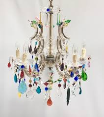 a 5 arm vintage marie therese chandelier decorated with multi coloured eclectic drops swags and flowers on the top of the arms