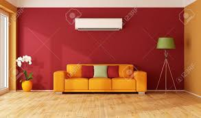 Red and orange living room with colorful sofa and air conditioner - 3D  Rendering Stock Photo
