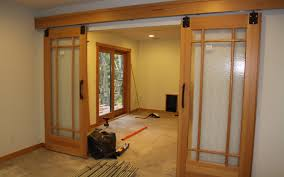 interior double sliding glass barn door frame with wooden track hanger and iron handle for living space remodeling