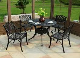 furniture black metal chairs with back and arms connected by round black metal table with