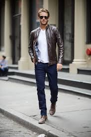 brown leather jacket with white t shirt and blue jeans