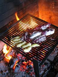 cooking at home over a wood fire placing fingerling potatoes and radicchio on grill to cook