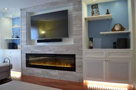 after clearlake fireplace wall with custom cabinetry and silver fox stone
