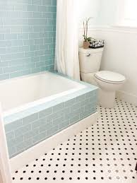 beautiful bathtub with tile tub surround and wall mount using bullnose tile and basketweave tile flooring