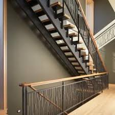 Contemporary Open Wood Staircase With Decorative Wrought Iron Rail Supports  Under Polished Wood Handrails