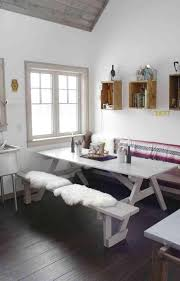 boho styled picnic nook with a dining table and benches covered with fur