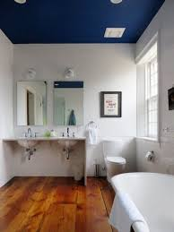 navy blue ceiling paint with stylish wooden laminate floor and nice tub for excellent bathroom design