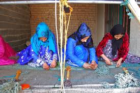 weavers at work on a horizontal loom weaving a pile carpet for the zollanvari company