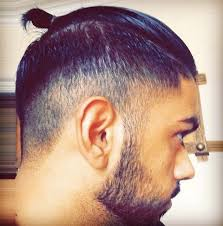 a male with a topknot hairstyle and 2 step undercut