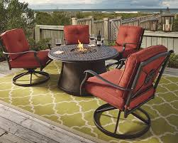 red outdoor dining set located on a dock that connects to a beach a fire