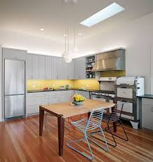 kitchen gray cabinets yellow backsplash light brown wooden island white pendant lights wide skylights from