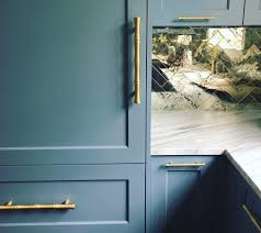 blue gray kitchen cabinets with gold bamboo style pulls