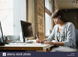 office space computer. Female Entrepreneur Working At Desk In Creative Office Space Computer