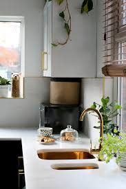 kitchen with black cupboards with white open shelving marble tiles gold sink and gold