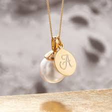 pearl necklace in gold with monogram charm off white pearl