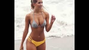arnte mujer en la playa luciendo i traje de baño