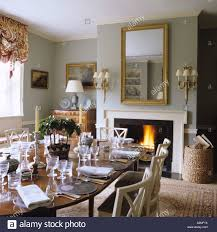 Dining Room With Laid Table And Lit Fire In English Country House - Country dining rooms