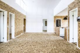 textural reclaimed materials contrast with white surfaces on the interior including cork tile floors bath tiles made of recycled glass and wall panels