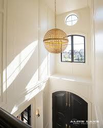 chic two story foyer features black arched front doors accented with brass plates illuminated by a gold globe pendant
