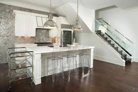 modern kitchen with white cabinets metal backsplash engineered hardwood floors and chrome pendant